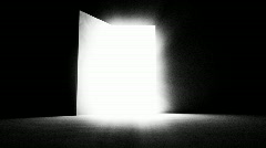 A black door opening and letting in white light.  Stock Footage
