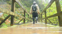 Man Hiking over Bridge in Rain 1 Stock Footage
