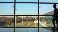 Silhouette of man walks against window at airport Stock Footage
