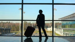 Silhouette of woman with travel luggage stands against window Stock Footage