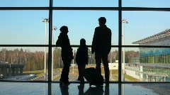 Silhouettes of family standing against window in building Stock Footage