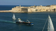 Stock Video Footage of Ships and boats passing Ricasoli Point at the entrance to Grand Harbour Valetta