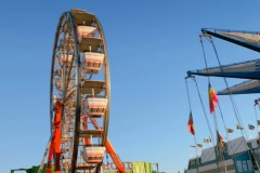 Stock Video Footage of Ferris wheel on carnival midway against blue sky