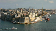 A boat passes Senglea to enter the Grand Harbour Valetta Stock Footage
