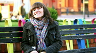 Attractive smiling woman sitting on bench in urban environment  Stock Footage