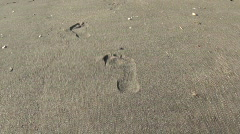 Following footprints in the sand - stock footage