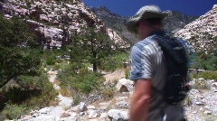 Solo Male Hiker Traveling into Desert Mountain Range Stock Footage