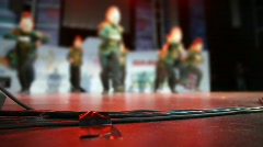 Focus on wires of audio equipment on floor of stage during dance routine Stock Footage