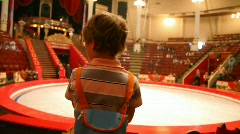 back view of boy stands against arena in circus after performance - stock footage