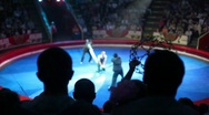 Stock Video Footage of silhoettes of audience looks at performance with gymnast in circus