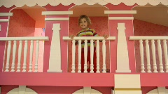 Girl stands on second level of children house Stock Footage