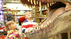 Kids looks at mouth of toy dinosaur Stock Footage