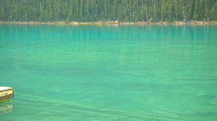 Lake Louise emerald green Water pan and tilt up to Forest mountain Stock Footage