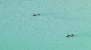 Two red Canoes Paddle across rippling Emerald Lake Stock Footage