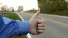 Man holding up thumb on side of road Stock Footage