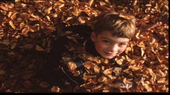 Boy in leaves (vintage 8 mm amateur film) Stock Footage