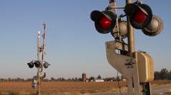 Railroad Crossing with Arms, Lights, and Passing Train Stock Footage