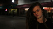 Dolly shot of pretty girl walking city street at night Stock Footage