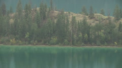 Kalamalka lake smooth Water zoom out reveals Rugged countryside Stock Footage