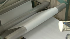 Paper rolls through printing press machine Stock Footage