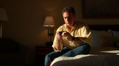 Man on bed texting and thinking Stock Footage