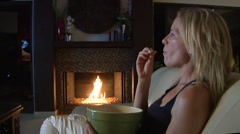 Pretty blonde woman eating popcorn watching TV by fireplace Stock Footage
