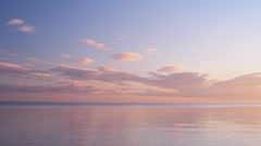 Sunset clouds timelapse over the calm sea - stock footage