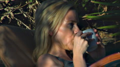 CU of pretty blonde woman on swing drinking coffee Stock Footage