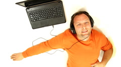 Man with headphones and laptop listening to music, isolated Stock Footage