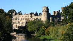 Towers and turrets of Warwick Castle stand high above the river Avon England UK - stock footage