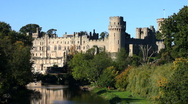 Stock Video Footage of Towers and turrets of Warwick Castle stand high above the river Avon England UK