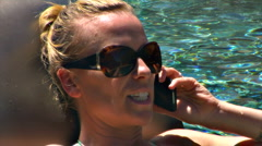 Pretty Blonde Woman in pool on mobile phone Stock Footage