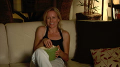 Pretty blonde woman laughs watching TV eating popcorn Stock Footage