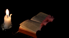 Reading the holy Bible by Candlelight Stock Footage