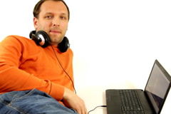 Man with headphones and laptop looking to camera, isolated Stock Footage