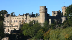 Towers and turrets of Warwick Castle stand high above the river Avon England UK Stock Footage