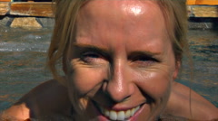 Pretty blonde Woman in spa breaks into smile for camera ECU Stock Footage