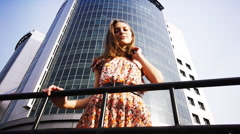Beautiful Girl in the background of a skyscraper 1 Stock Footage