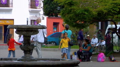 Family blows bubbles Guatemalan park Stock Footage