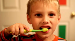 Dolly shot of young boy brushing teeth Stock Footage