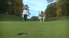 Female golfer barely misses putt (view from hole) Stock Footage