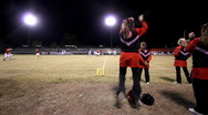 Dolly shot of football game with cheerleaders Stock Footage