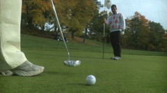 Golfer makes putt and celebrates with partner - stock footage