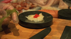 Sushi chef garnishing scallop sashimi Stock Footage