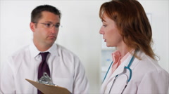 Woman doctor taking notes from a paitent Stock Footage