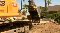 Excavator digging hole on suburban street Stock Footage