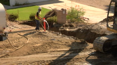 Construction worker spays water on dirt to prevent dust Stock Footage