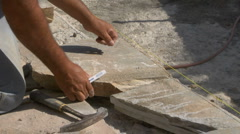 Stonemason places and marks natural stone coping Stock Footage