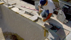 Stonemason hammering pool coping with chisel Stock Footage