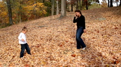 Dolly shot of mother and son playing in leaves Stock Footage